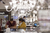 Shoppers browse jewelry displayed on a counter underneath chandeliers at Harrods luxury department store in London UK on Monday June 24 2013 Harrods...