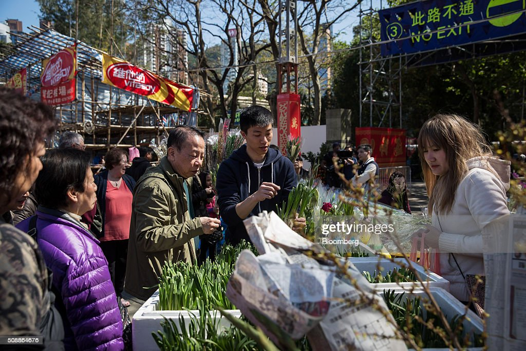 Shoppers browse narcissus flowers displayed for sale for the Lunar New Year at a flower market in Victoria Park in Hong Kong, China, on Sunday, Feb 7, 2016. The city's financial markets will close on Feb. 8 for the Lunar New Year holidays and resume trading on Feb. 11. Photographer: Billy H.C. Kwok/Bloomberg via Getty Images