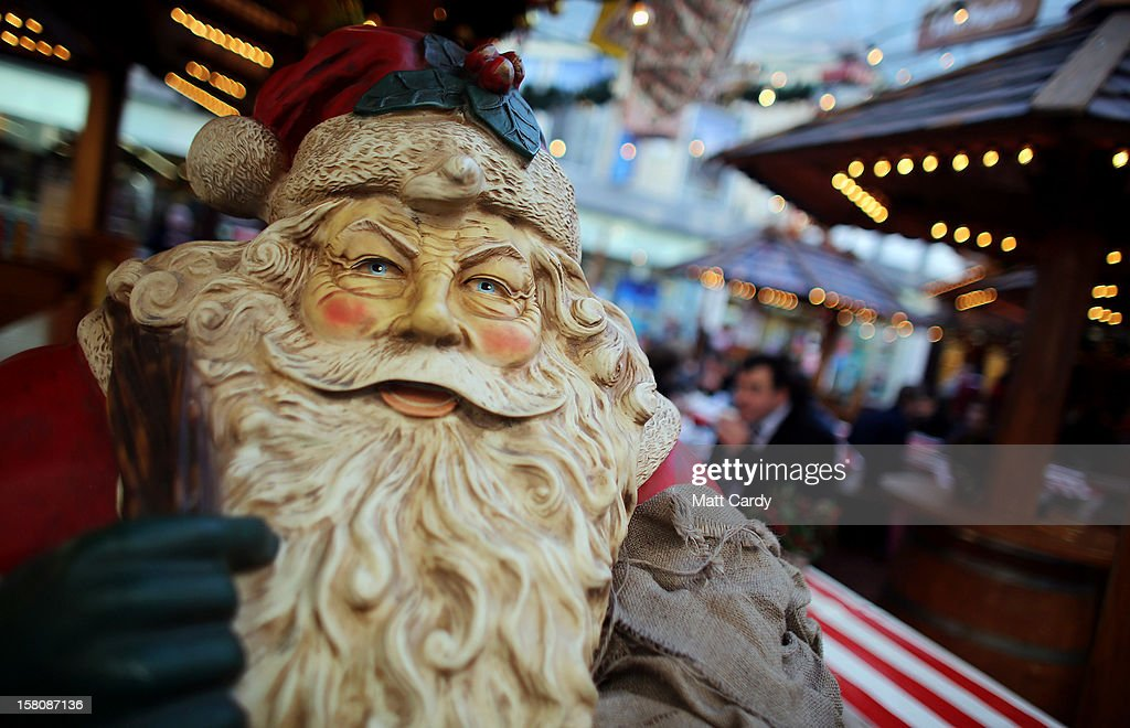 Shoppers browse stalls next to a Santa Claus decoration at a Christmas market on December 10, 2012 in Bristol, England. With internet shopping still on the rise, many traditional retailers claim this Christmas could be the one that will determine the future of the high street.