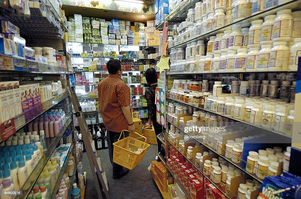 Shoppers browse through the aisles of medicines and health supplements at a pharmacy in Singapore on Wednesday Feb 13 2008 Singapore's industrial...