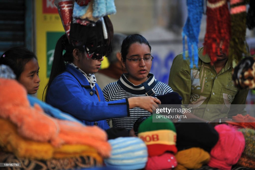 Shoppers browse through woolen hats during a cold day in Siliguri on January 9, 2013. As thousands of homeless people sought places in temporary shelters, the unusual cold in throughout India has been attributed to dense fog which has obscured the sun and disrupted airports and trains, as well as icy winds from the snowy Himalayas to the north. AFP PHOTO/Diptendu DUTTA