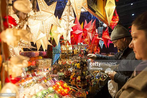 Shoppers browse trinkets on a stall during a Christmas market at the main railway station in Zurich Switzerland on Thursday Nov 26 2015 The Swiss...