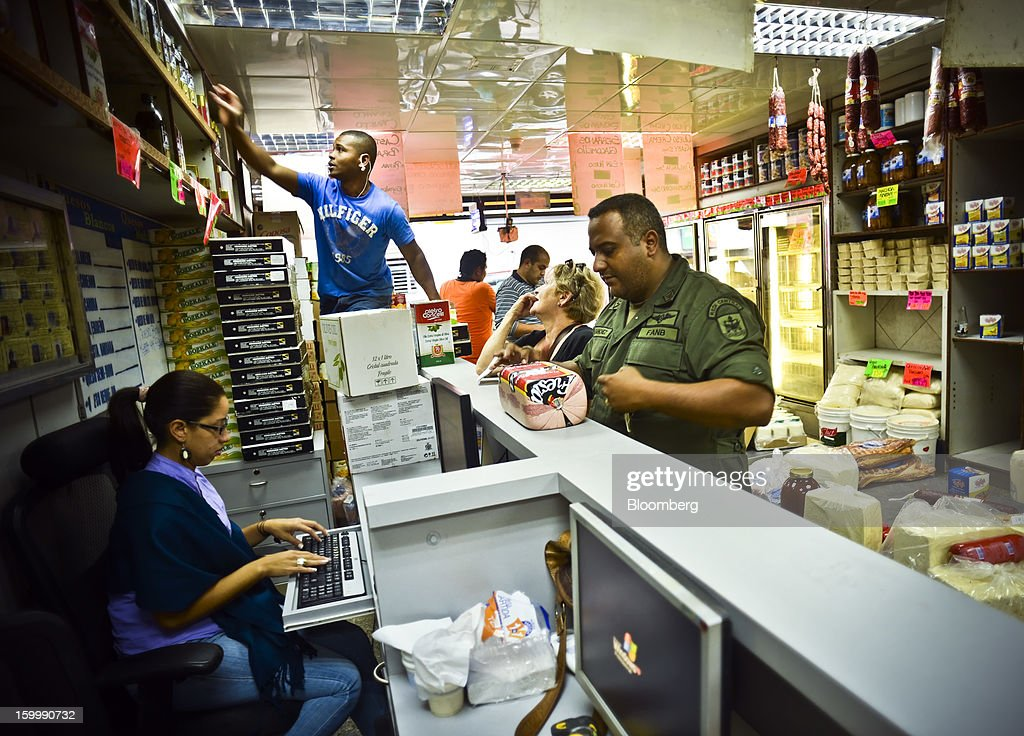 Shoppers buy meat and cheese after waiting for more than 30 minutes in line at a private sector grocery store in the Quinta Crespo market in central Caracas, Venezuela, on Monday, Jan. 14, 2013. The government is conducting a nationwide campaign to crack down on over-pricing and hoarding it blames for shortages of basic goods, from toilet paper to sugar. Photographer: Meridith Kohut/Bloomberg via Getty Images