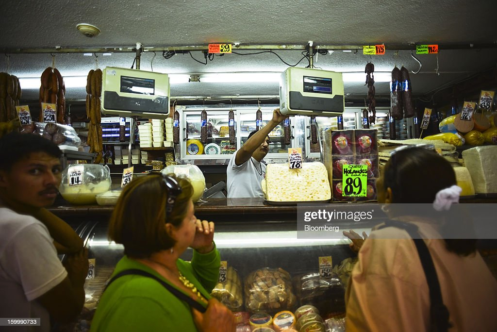 Shoppers buy meat and cheese for sale at a butcher shop in central Caracas, Venezuela, on Monday, Jan. 14, 2013. The government is conducting a nationwide campaign to crack down on over-pricing and hoarding it blames for shortages of basic goods, from toilet paper to sugar. Photographer: Meridith Kohut/Bloomberg via Getty Images