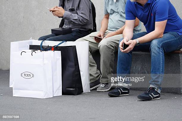 Shoppers carry a Tod's and Hugo Boss bags at Outletcity Metzingen on August 19 2016 in Metzingen Germany Metzingen is famous for its factory outlets...