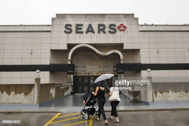 Shoppers carry an umbrella while walking towards a Sears Canada Inc store inside a mall in Toronto Ontario Canada on Thursday June 22 2017 Canadian...