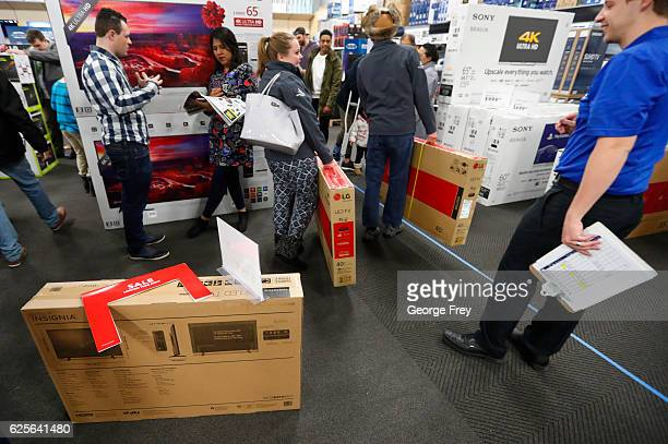 Shoppers carry away televisions at a Best Buy store that were on sale as part of 'Black Friday' deals on November 24 2016 in Orem Utah Retailers...