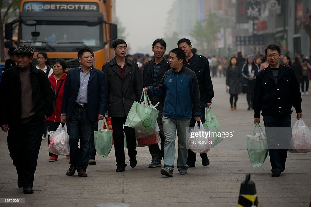 Shoppers carry bags as they walk on a popular shopping street in Beijing on April 23, 2013. Manufacturing activity in China slowed in April due to sluggish foreign demand, HSBC said, in a sign of further weakness in the world's second-largest economy. AFP PHOTO / Ed Jones