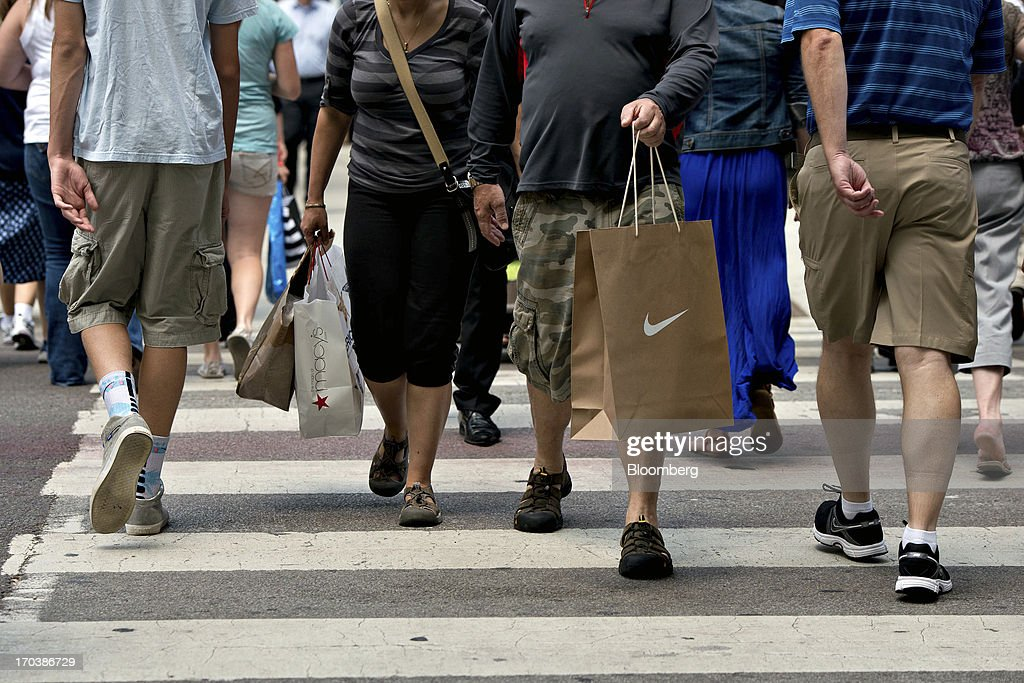 Shoppers carry bags as they walk through a retail area known as the 'Magnificent Mile' in Chicago, Illinois, U.S., on Tuesday, June 11, 2013. Sales at U.S. retailers probably rose in May as an improving job market gave consumers the confidence to shop for automobiles, home furnishings and clothing, economists said before reports this week. Photographer: Daniel Acker/Bloomberg via Getty Images