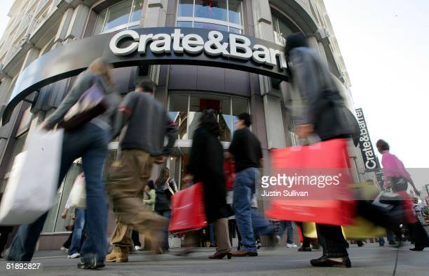 Shoppers carry bags as they walk through the Union Square shopping district December 24 2004 in San Francisco California Retailers suffering with...