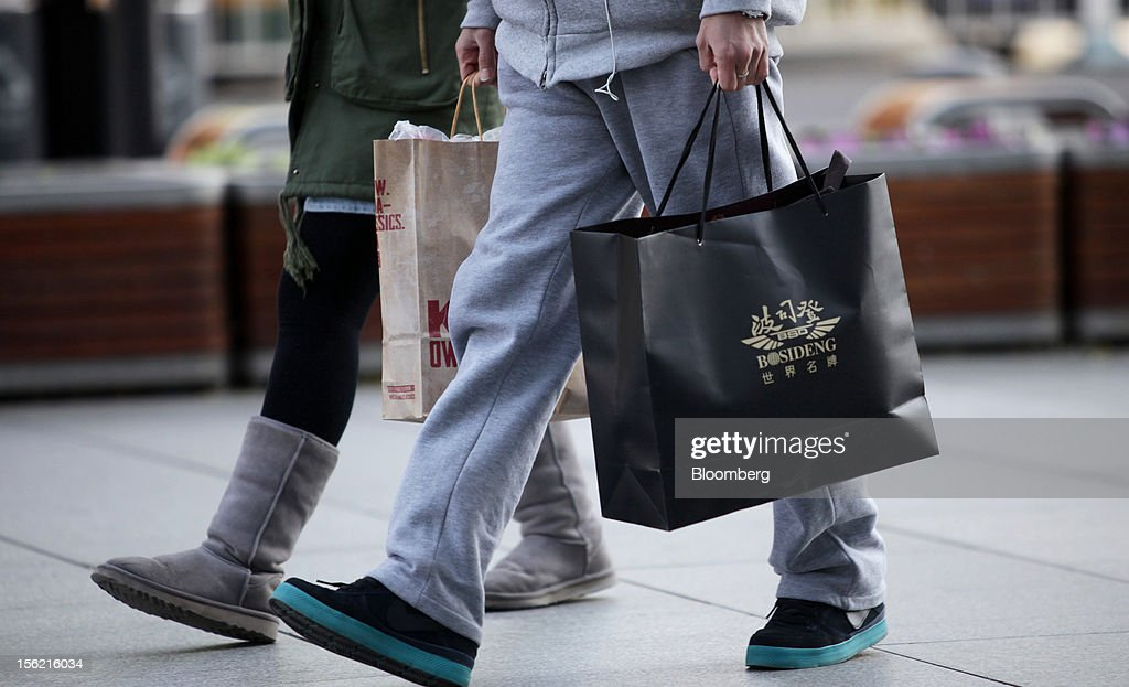 Shoppers carry bags at a shopping district in Beijing, China, on Sunday, Nov. 11, 2012. China's retail sales exceeded forecasts and inflation unexpectedly cooled to the slowest pace in 33 months, signaling the government is boosting growth without driving a rebound in prices. Photographer: Tomohiro Ohsumi/Bloomberg via Getty Images