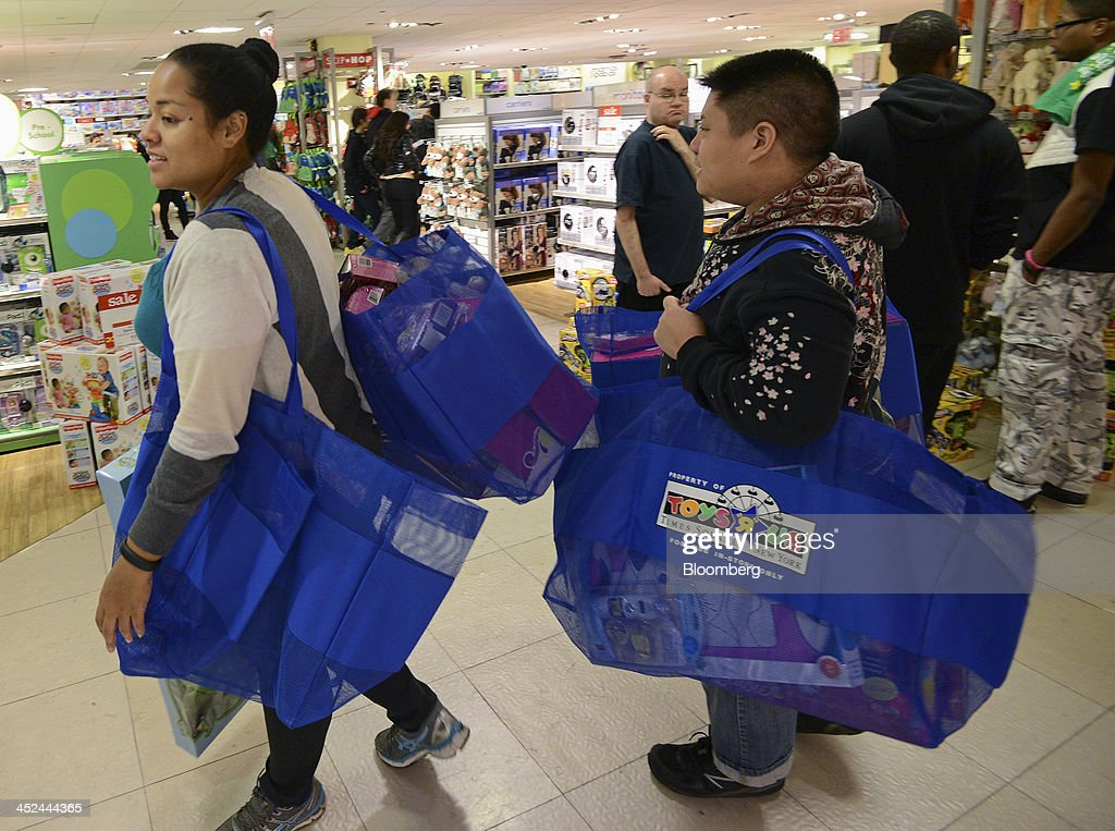 Shoppers carry bags filled with merchandise while walking through a Toys R Us Inc. store ahead of Black Friday in New York, U.S., on Thursday, Nov. 28, 2013. U.S. retailers will kick off holiday shopping earlier than ever this year as stores prepare to sell some discounted items at a loss in a battle for consumers. Photographer: Peter Foley/Bloomberg via Getty Images