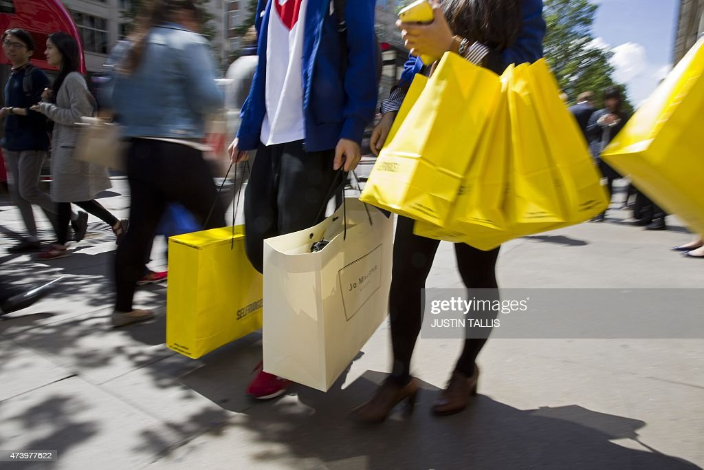 Shoppers carry bags from a Selfridges store as they walk along ...