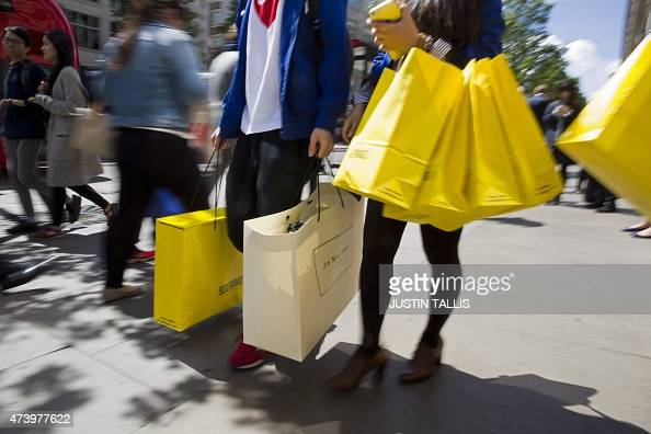 Shoppers carry bags from a Selfridges store as they walk along Oxford Street in central London on May 19 2015 Britain's annual inflation rate sank...