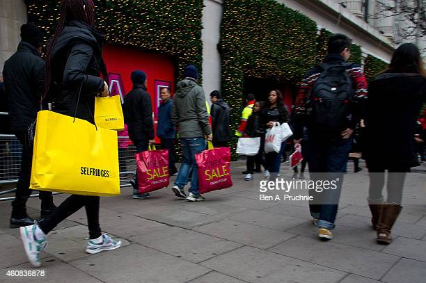 Shoppers carry bags on Oxford Street during the annual boxing day sales on December 26 2014 in London England
