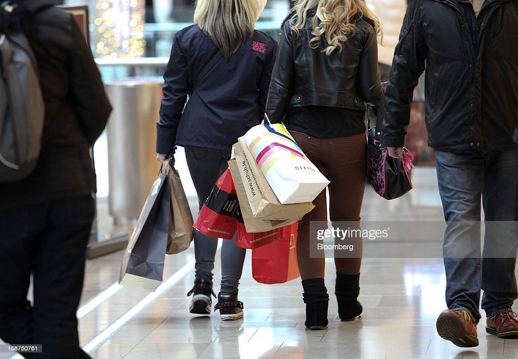 Shoppers carry goods in branded bags as they walk through through the Westfield Stratford City shopping mall in London, U.K., on Thursday, Dec. 27, 2012. Overall Christmas shopping in the U.K. was similar to last year, according to the British Retail Consortium. Photographer: Chris Ratcliffe/Bloomberg via Getty Images