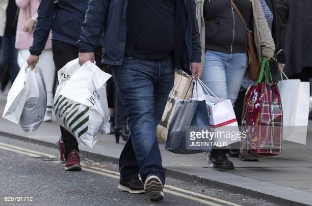 Shoppers carry plastic bags containing purchases from John Lewis and other retail stores as they walk along Oxford Street on 'Black Friday' in London...