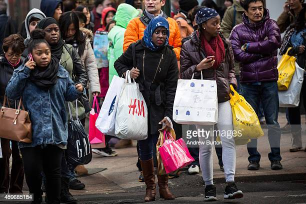 Shoppers carry recent purchases through Herald Square on the morning of November 28 2014 in New York City The Friday after Thanksgiving also known as...