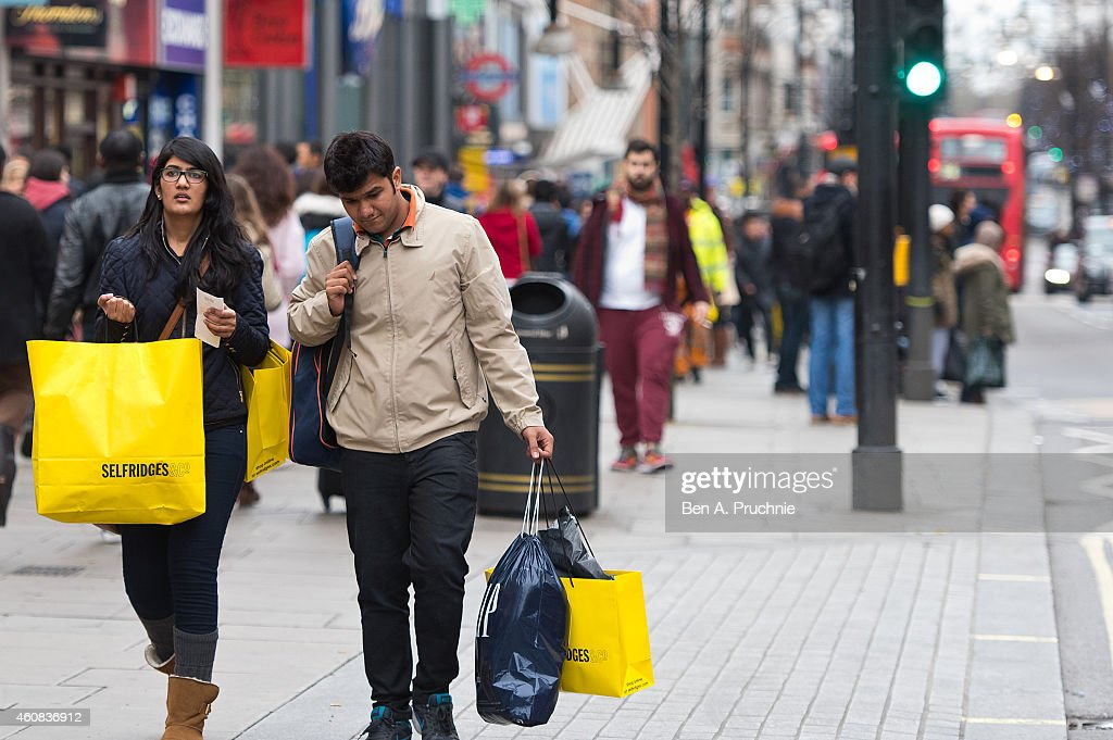 Shoppers carry Selfridges bags on Oxford Street during the annual boxing day sales on December 26 2014 in London England