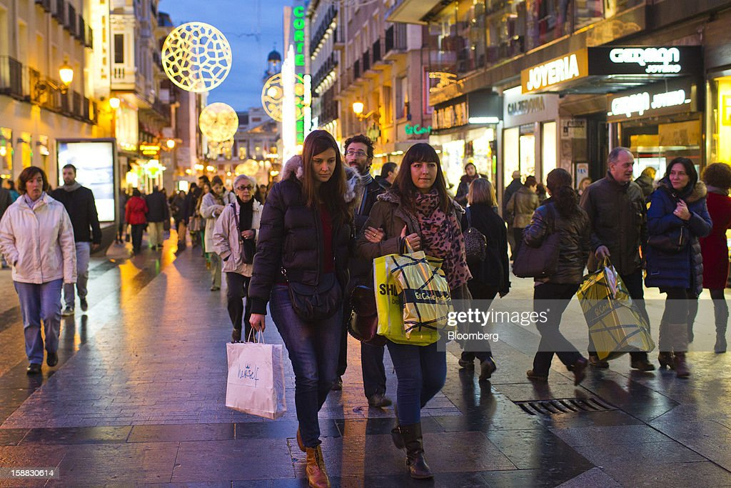 Shoppers carry their purchases past stores in central Madrid, Spain, on Saturday, Dec. 29, 2012. Spain's economic activity kept falling in the fourth quarter, Bank of Spain says. Photographer: Angel Navarrete/Bloomberg via Getty Images