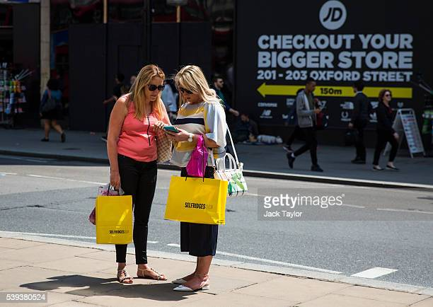 Shoppers carrying Selfridges bags check their phone on Oxford Street on June 9 2016 in London England Conditions are tough for the High Street as...