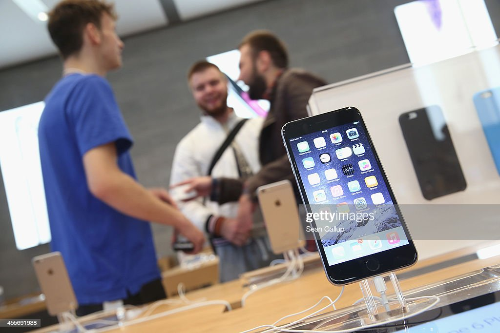Shoppers chat with a sales assitsant as a new Apple iPhone 6 Plus stands on display at the Apple Store on the first day of sales of the new phone in...
