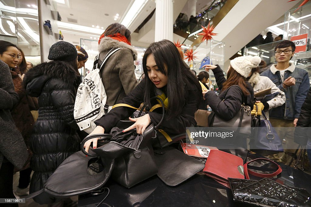 Shoppers check out handbags as they crowd inside the Selfridges department store in central London, on December 26, 2012, in search of a bargain during the post Christmas Boxing Day sales. Hundreds of thousands of bargain hunters headed to the shops for the traditional Boxing Day sales despite strike action on London's underground train network. AFP PHOTO / JUSTIN TALLIS