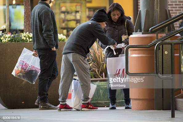 Shoppers check their receipts for items purchased at a Hennes Mauritz AB store in Emeryville California US on Monday Dec 26 2016 The Bloomberg...