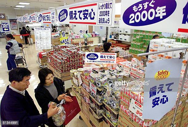 Shoppers choose food and the other necessities of life at a Tokyo supermarket 29 December 1999 in preparation for possible stoppage of electricity...