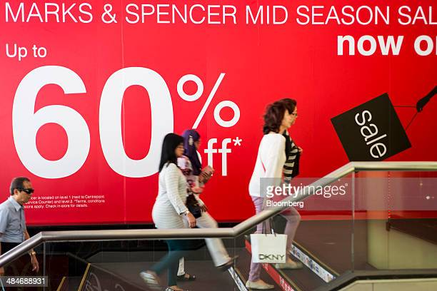 Shoppers climb a flight of stairs past an advertisement for a mid season sale at a Marks Spencer Group Plc store on Orchard Road in Singapore on...