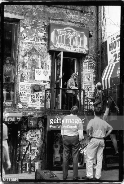 Shoppers climb the steps of the posterencrusted facade of Trash and Vaudeville clothing and accessories store New York New York 1992