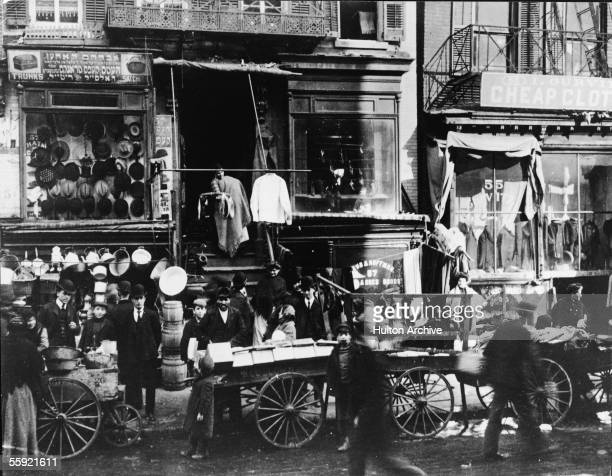 Shoppers congregate as vendors sell their wares on the sidewalk outside of haberdasheries at 57 Hester Street and 55 Hester Street on the Lower East...