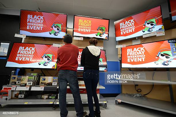 Shoppers consider televisions for sale at the Walmart in the Crenshaw district of Los Angeles on Black Friday November 29 2013 AFP PHOTO / Robyn Beck