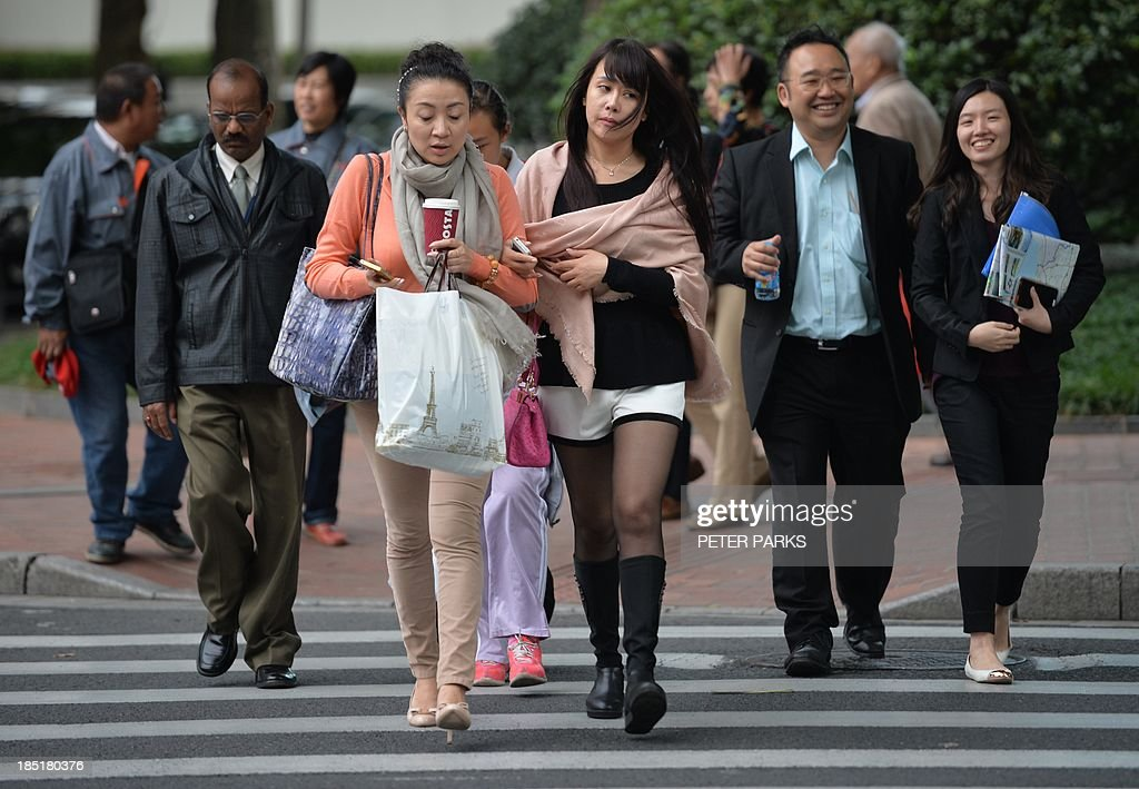 Shoppers cross an intersection in a commercial district of Shanghai on October 18, 2013. China's economy expanded 7.8 percent year-on-year in July-September, data showed, snapping two quarters of slowing growth, but analysts questioned whether the improvement was sustainable. AFP PHOTO / Peter PARKS