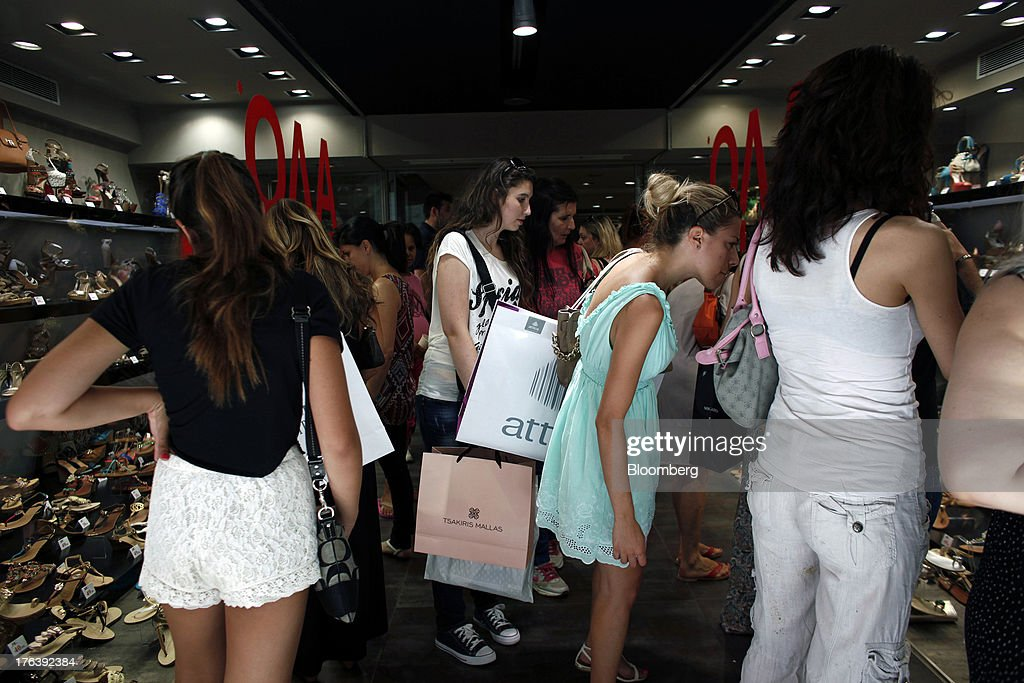 Shoppers crowd to look at shoes inside a store offering sales discounts in Athens, Greece, on Saturday, Aug. 10, 2013. Greece's economy contracted for a 20th quarter, extending an economic slump that has left more than six in 10 young Greeks out of work. Photographer: Angelos Tzortzinis/Bloomberg via Getty Images