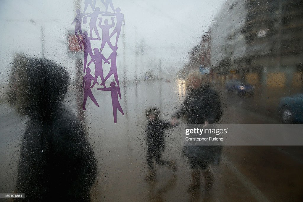 Shoppers dash for sheler in a bus stop as they brave gale force winds on December 23, 2013 in Blackpool, United Kingdom. The Met Office has issued a number of severe weather warnings for heavy rain and high winds and is warning that it may lead to some travel disruption as people make their journeys for Christmas.
