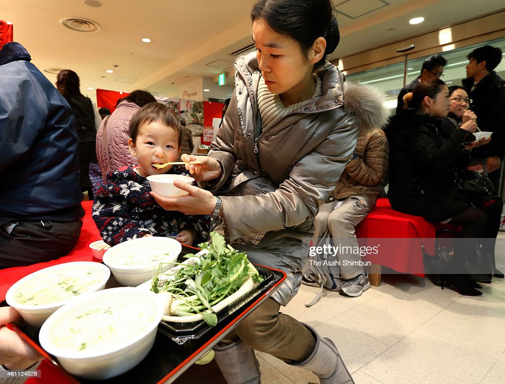 Shoppers enjoy the 'Nanakusa-Gayu', seven-herb rice porridge offered ...