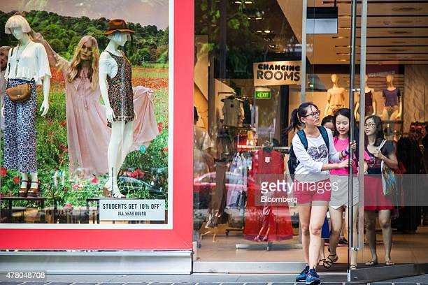 Shoppers exit a Topshop stores operated by Arcadia Group Plc on Orchard Road in Singapore on Sunday June 21 2015 Consumer prices prices declined for...