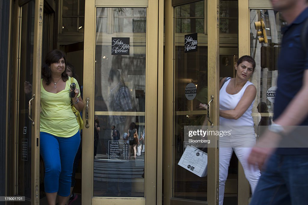 Shoppers exit Saks Fifth Avenue in New York, U.S., on Monday, July 29, 2013. Hudson's Bay Co. agreed to buy Saks Inc. for $2.4 billion, combining Canada's largest-department store chain with one of the most prestigious U.S. luxury retailers in a deal that may spur the creation of a real estate investment trust. Photographer: Scott Eells/Bloomberg via Getty Images