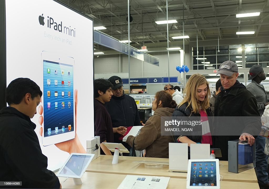 Shoppers gather around a display for the Apple ipad mini inside of a Best Buy store during their Black Friday sale which started at midnight on November 23, 2012 in Rockville, Maryland. Thanksgiving, the last US holiday undisturbed by mass commercialization, is now victim to the ever advancing Christmas shopping season, with stores welcoming shopaholics before the family turkey can be taken from the oven.