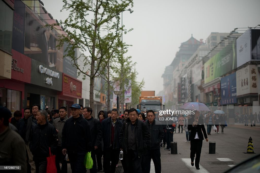 Shoppers gather as they walk on a popular shopping street in Beijing on April 23, 2013. Manufacturing activity in China slowed in April due to sluggish foreign demand, HSBC said, in a sign of further weakness in the world's second-largest economy. AFP PHOTO / Ed Jones