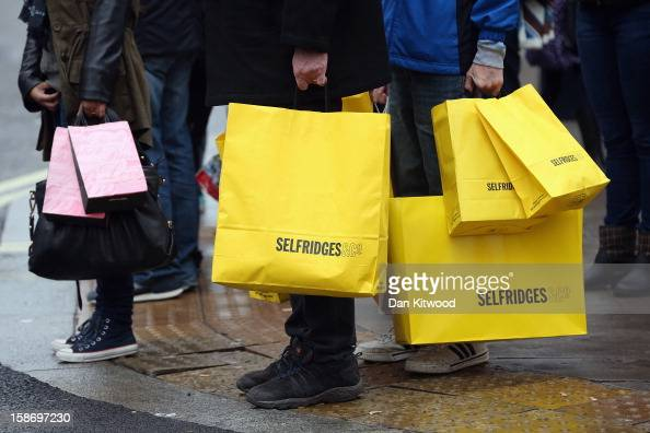 Shoppers hold bags on Regent Street on December 24 2012 in London England Many high street retailers have started their sales two days early this...