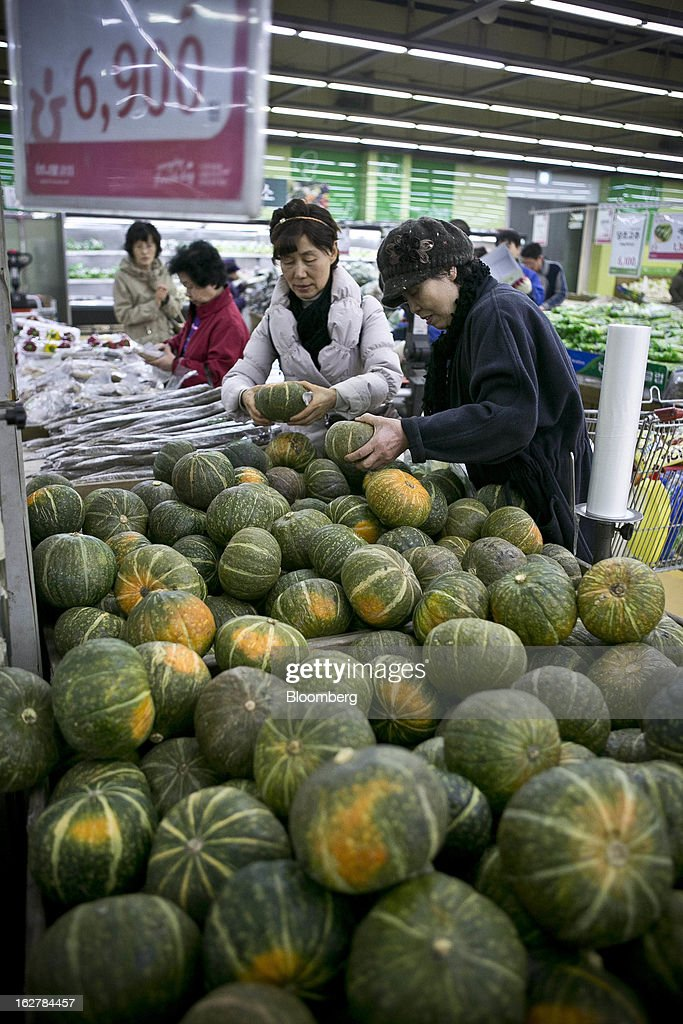 Shoppers hold pumpkins at Hanaro Mart in Seoul, South Korea, on Tuesday, Feb. 26, 2013. South Korean consumer confidence remained at its highest level since May as gains in the won drove down the prices of imported goods. Photographer: Jean Chung/Bloomberg via Getty Images