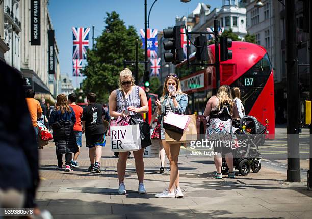 Shoppers holding their bags pause on Oxford Street on June 9 2016 in London England Conditions are tough for the High Street as retailers recorded a...