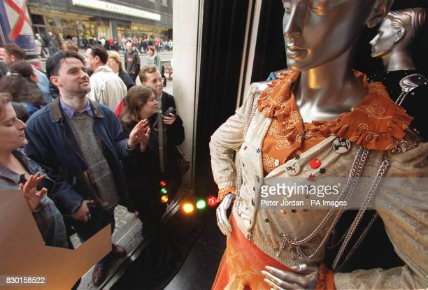Shoppers in London's Oxford Street view the original costumes worn by Abba on the night the group won the 1974 Eurovision Song Contest on display at...