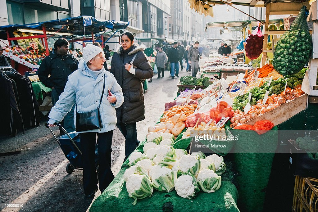 CONTENT] Shoppers inspect fresh fruit and vegetables at one of the many vendor stalls along Surrey Street Market in the London Borough of Croydon, United Kingdom.