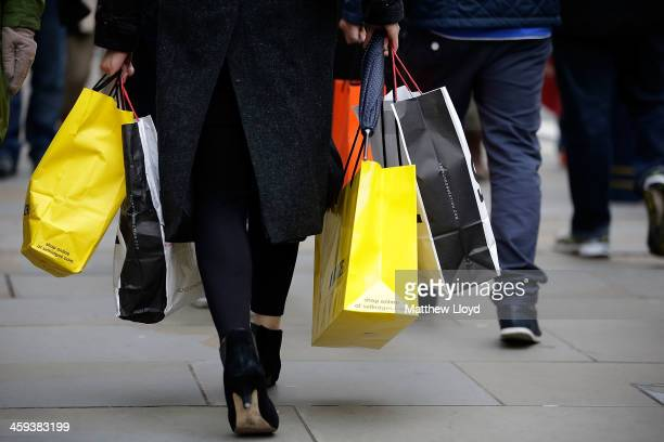 Shoppers laiden with carrier bags walk down Regents Street during the Boxing Day sales on December 26 2013 in London England Statistics have shown...