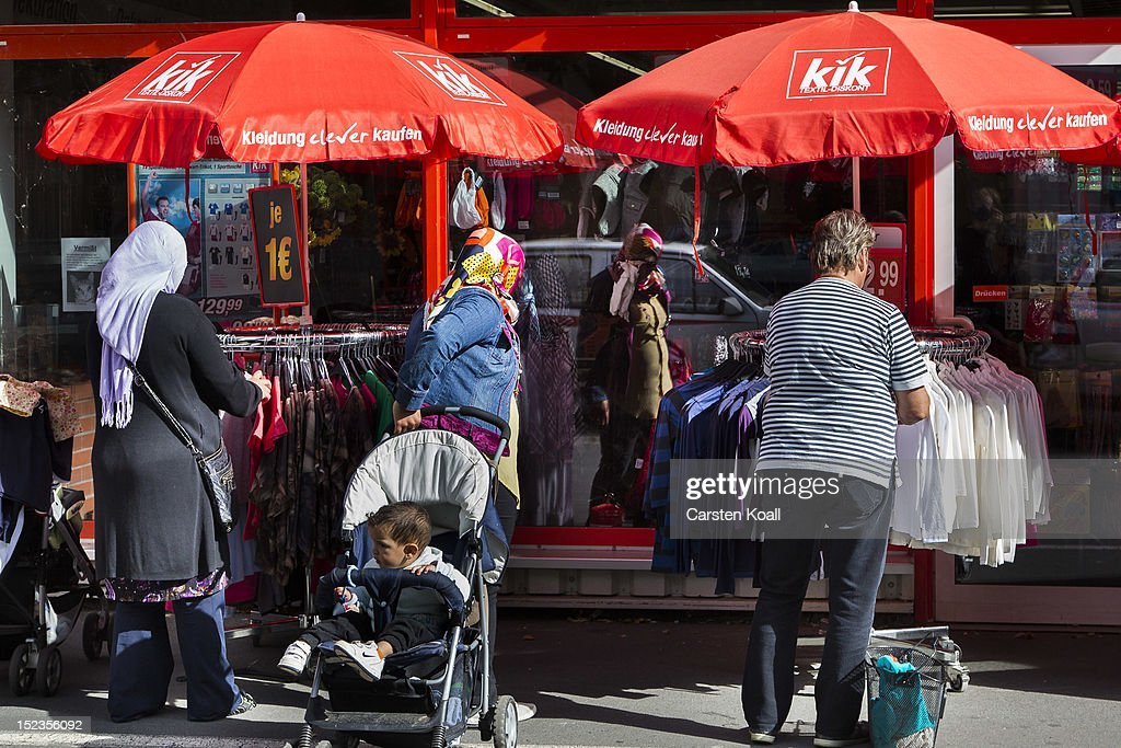 Shoppers look among clothes on display outside a Kik discount textiles store on September 18, 2012 in Berlin, Germany. Kik, a nationwide discount clothing chain in Germany, is reportedly among the companies that sourced some of its production to the garment factory in Karachi, Pakistan, that recently burned down, killing at least 258 people.