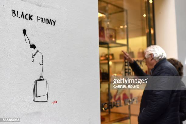 Shoppers look at a display window next to a street art depicting the 1968 Olympics Black Power salute along with shopping bags during 'Black Friday'...