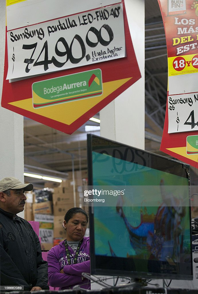 Shoppers look at a flat screen television under signs with discounted prices inside a Wal-Mart de Mexico SAB de CV's Bodega Aurrera store in Mexico City, Mexico on Saturday, Nov. 17, 2012. El Buen Fin, Mexico's equivalent of Black Friday, when the year's biggest discounts are offered by participating stores, is held on the third weekend of November and will run through Nov. 19. Photographer: Susana Gonzalez/Bloomberg via Getty Images